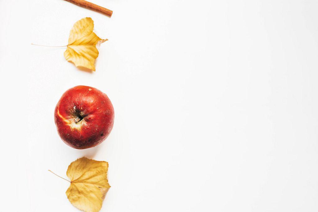 Aufsicht - Herbstmotiv - Ein Roter Apfel mit gelben Blättern und einer Zimtstange in Linie auf weißem Hintergrund