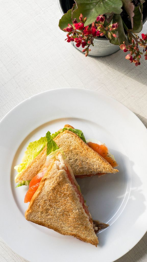 Aufsicht - Sandwichecken mit geräuchtertem Lachs, Tomate und Salat auf einem weißen Teller