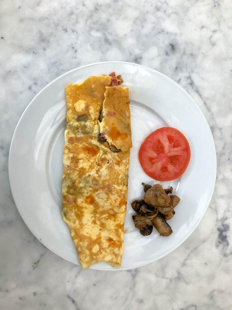Aufsicht - Schinken-Pilz Omelette mit Pilzen und einer Scheibe Tomaten auf einem weißen Teller