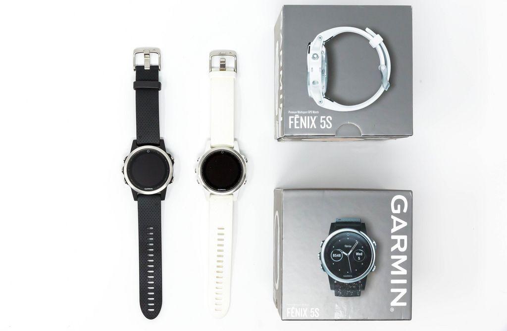 Aufsicht von Garmin Fenix 5S Smartwatches in schwarz und weiß mit Verpackung auf weißem Hintergrund