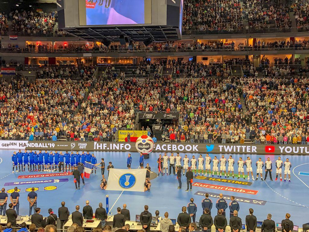 Aufstellung der Mannschaften vor Handballspiel auf Handballfeld in Stadion voller Fans
