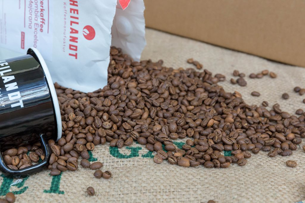 Aus Beutel ausgekippte, aromatisch geröstete Kaffeebohnen mit Kaffeetasse auf Jutesack