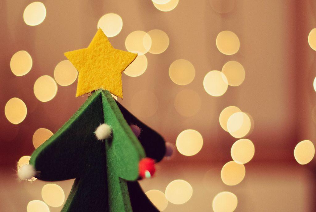 Aus Filz hergestellter Weihnachtsbaum mit Stern auf der Spitze vor Lichtermeer
