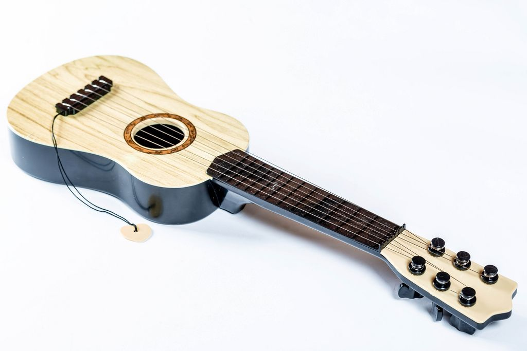 Aus hellbraunem Holz gefertigte, liegende Gitarre vor weißem Hintergrund