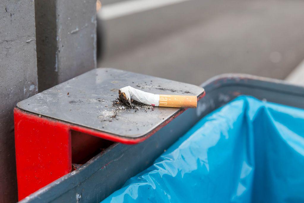 Ausgedrückte Zigarette der Marke Marlboro liegt auf metallener Halterung eines Mülleimers
