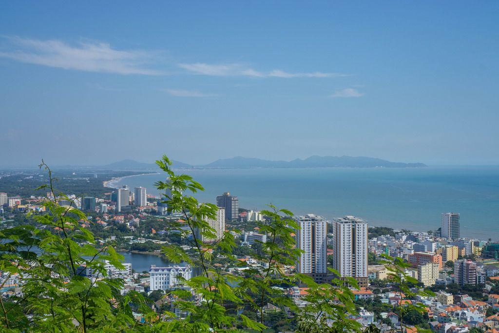 Aussicht auf die Küste der Stadt Vung Tau in Vietnam mit dem dahinter liegenden Strand und Bergen im Hintergrund