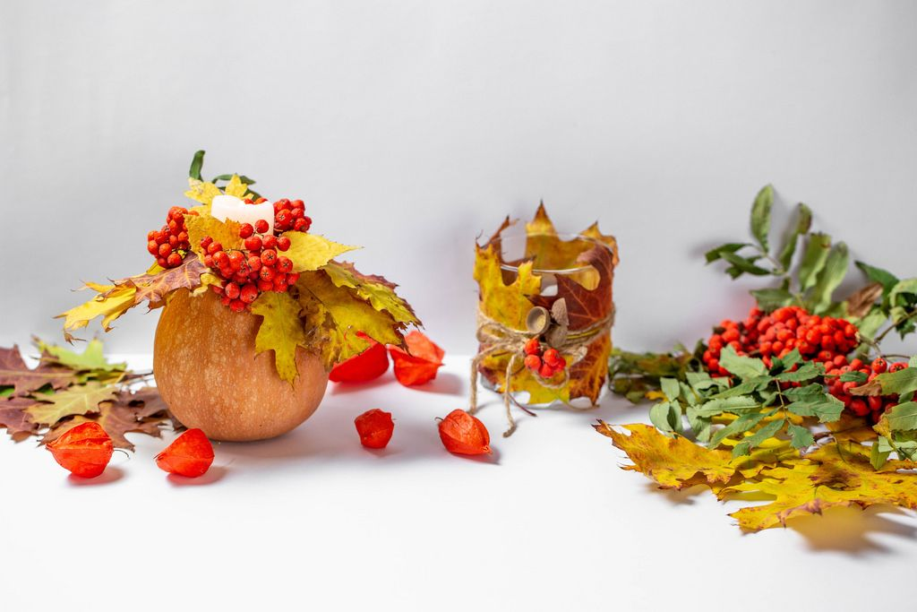 Autumn Decorations - Pumpkin with a candle, red berries, yellow leaves and physalis on white background