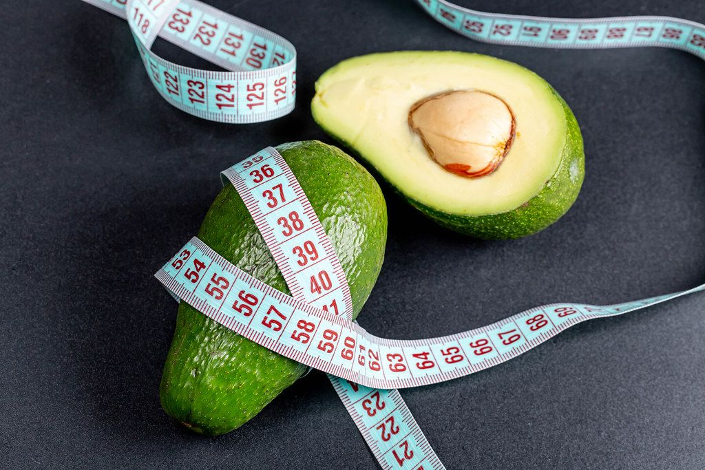 Avocado and measuring tape on a black background. The concept of weight loss