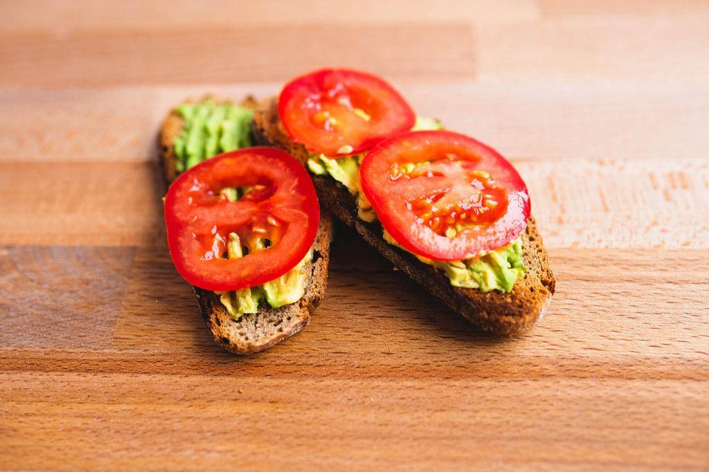 Avocado and tomatoes sandwiches on rye bread on wooden board