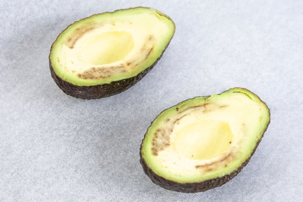 Avocado sliced on the half on the baking paper