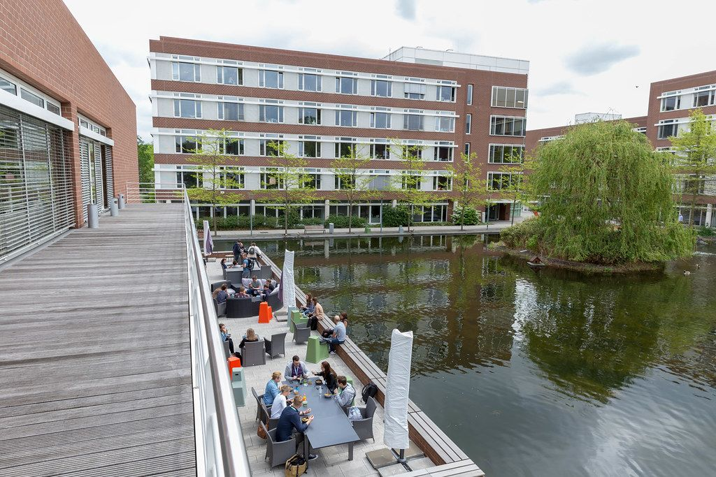 AXA-House in Cologne, Germany at Colonia-Allee with people relaxing on a terrace deck at a lake with a small island.