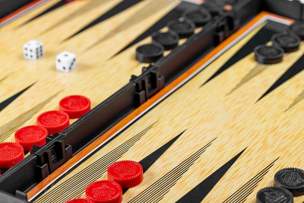 Backgammon board with black and red checkers and dice (Flip 2019)