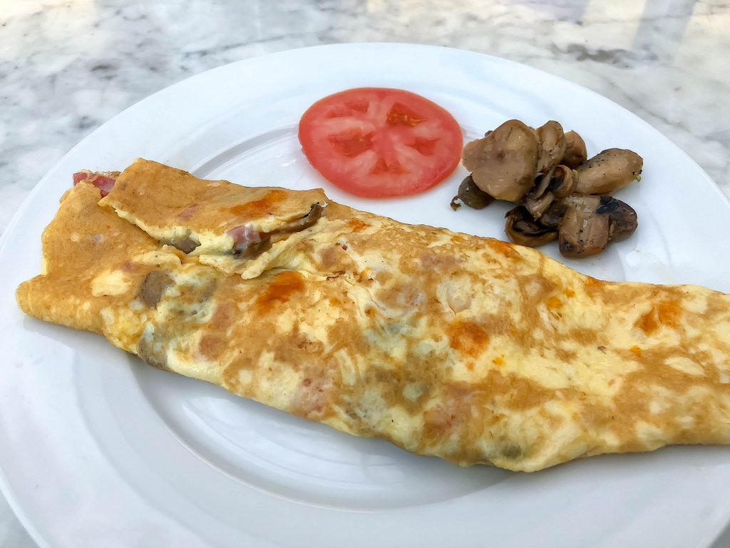 Bacon-mushrooms Omelette witch grilled mushrooms and a slice of tomato on the side