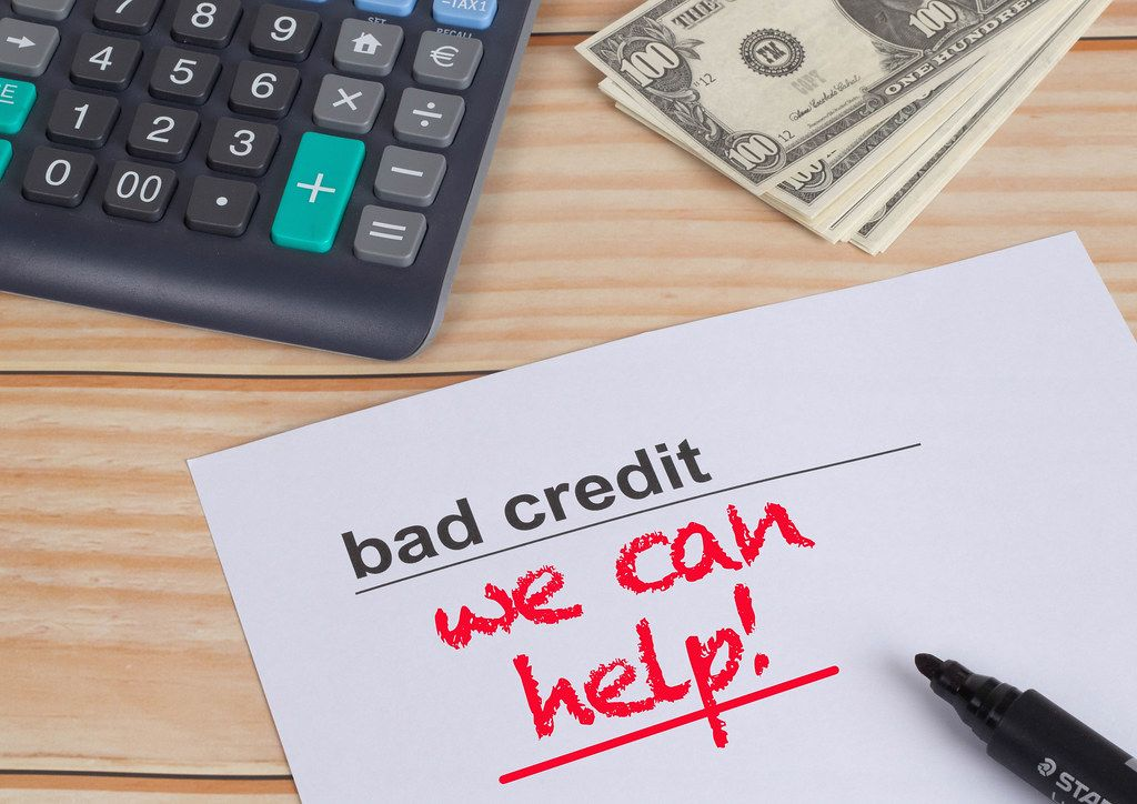 Bad Credit, we can help text with money and calculator on wooden table