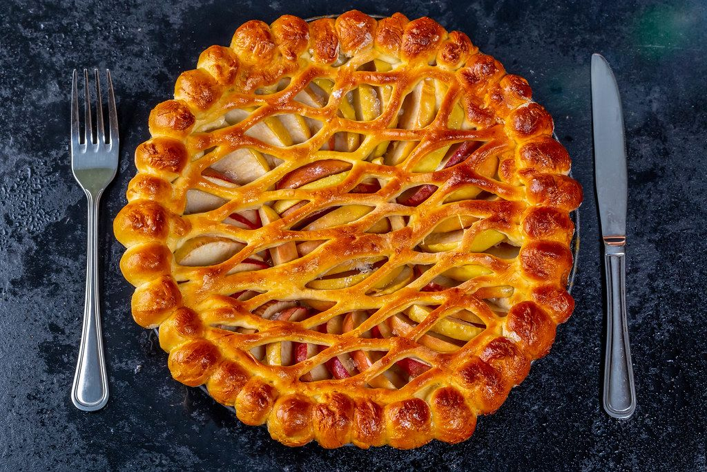 Baked Apple pie with knife and fork. Top view