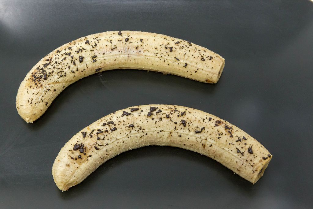 Baked Bananas with melted chocolate on black plate
