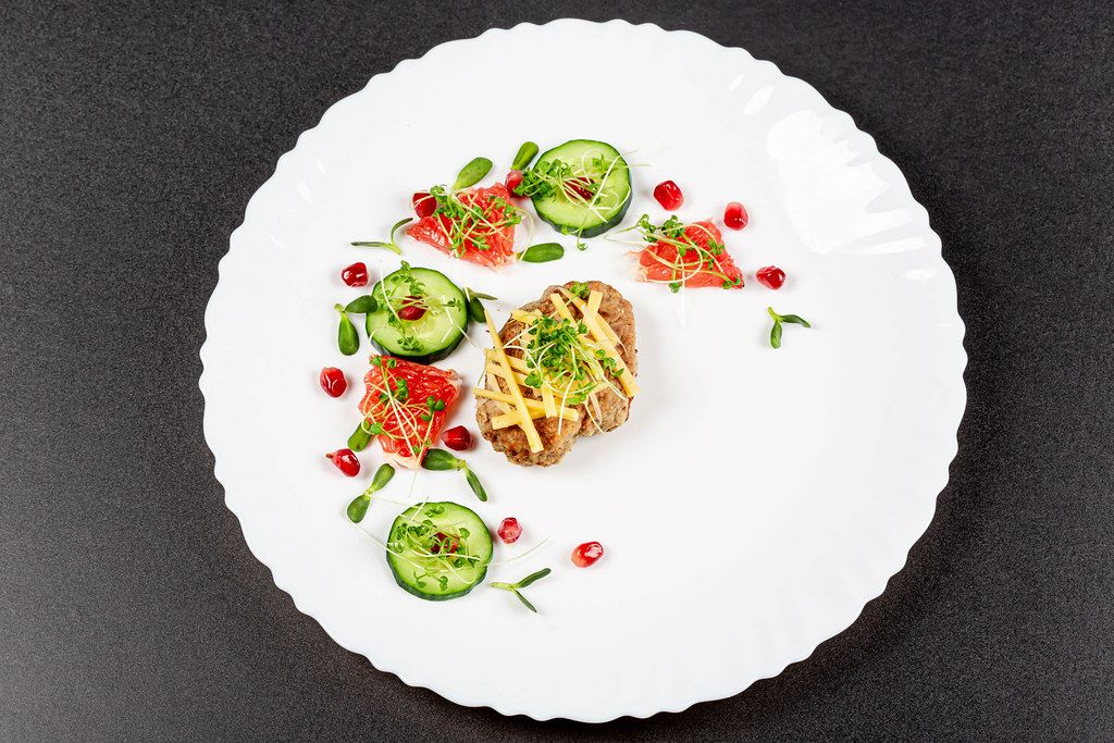 Baked chicken with grated cheese and a garnish of cucumber, micro greens and fruits, top view