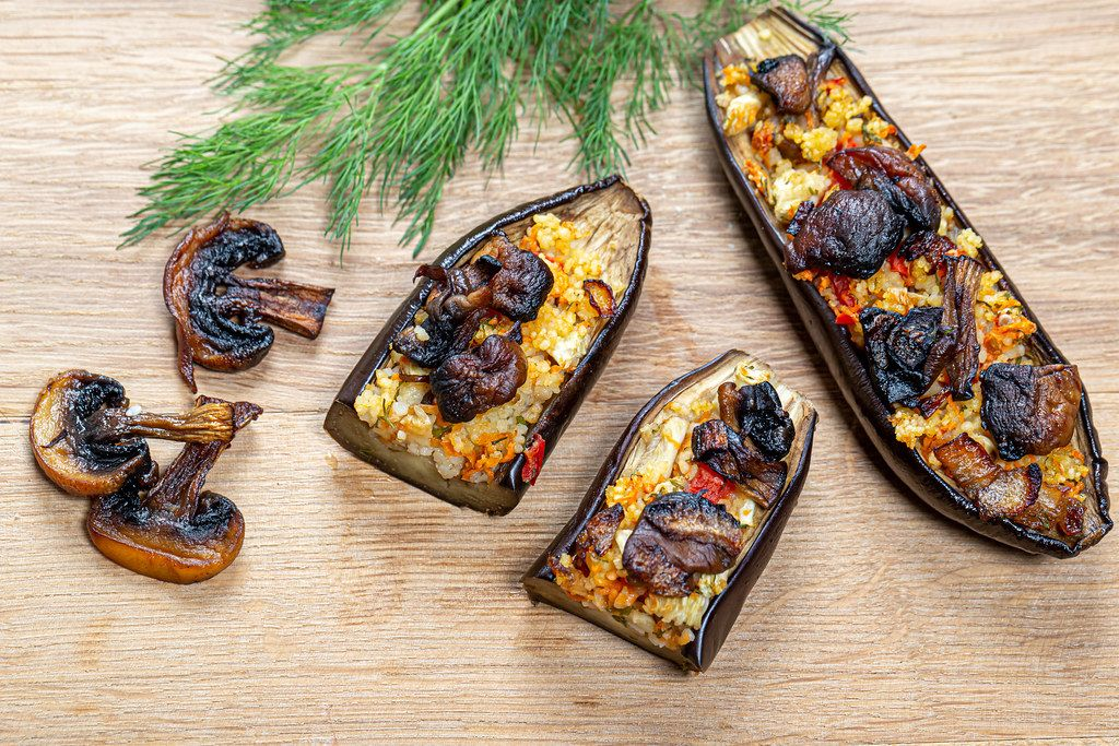 Baked eggplant with vegetables, couscous and mushrooms on a wooden background. Top view