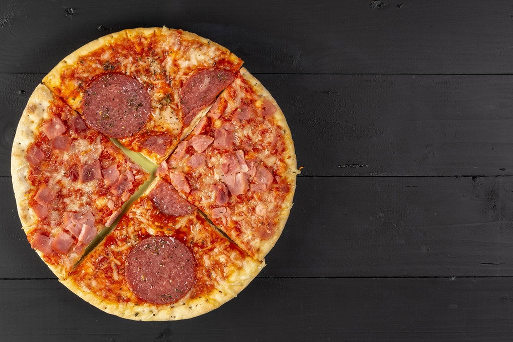 Baked Pizza with Sausage on the black wooden table (Flip 2019)