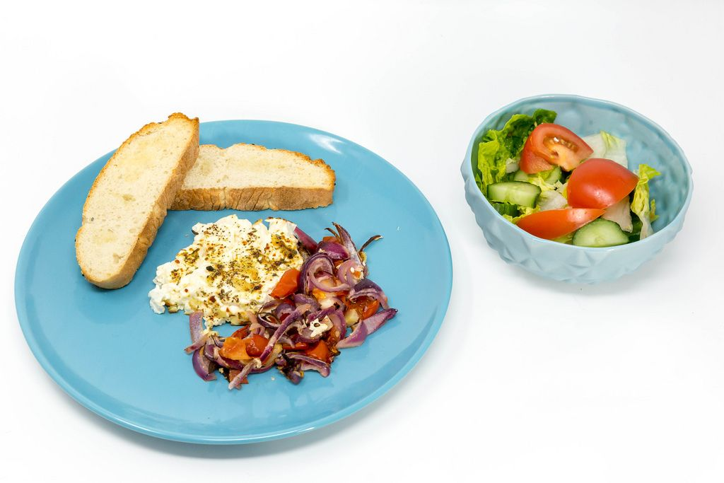 Baked shepherds cheese with tomatoes-onion stew and garlic bread on a blue plate and a fresh mixed salat on white background