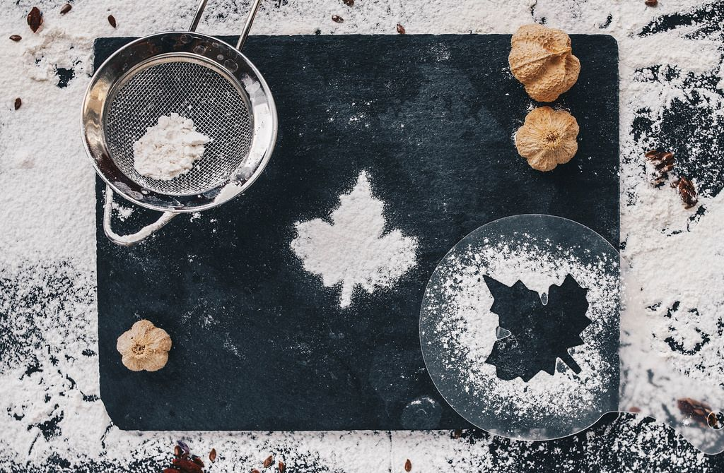 Baking backround with flour and leaf shape on black kitchen table. Top view