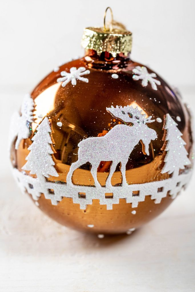Ball for a Christmas tree with an ornament of trees and a deer