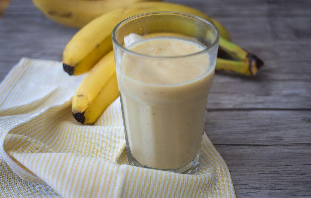 Bananen-Smoothie in einem Glas mit Bananen im Hintergrund auf einem Küchentuch