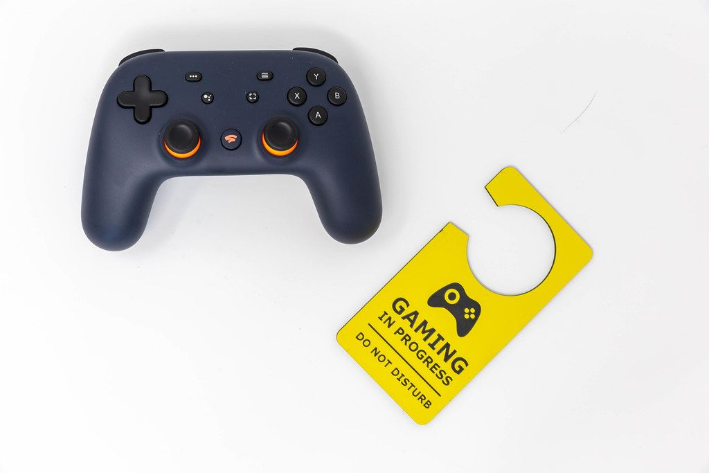Basic equipment for gaming: Stadia video game controller and yellow door hanger