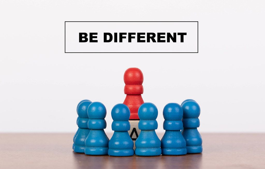 Be different concept with pawn figurines on table