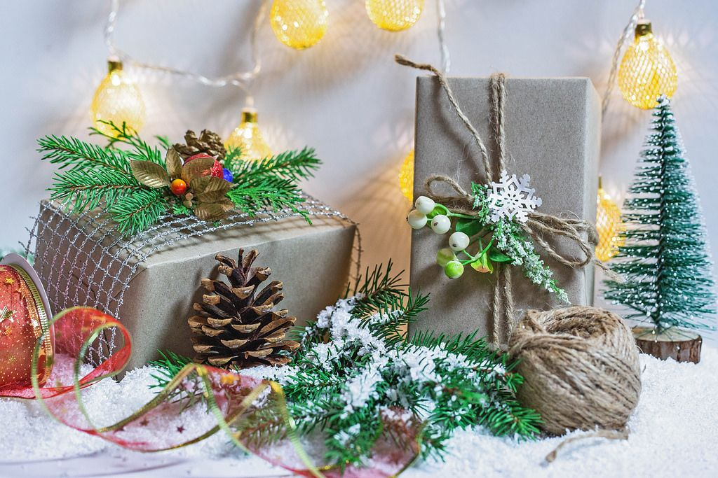 Beautiful decorated gift boxes and New Year's décor with a Christmas tree, snow and luminous garland.