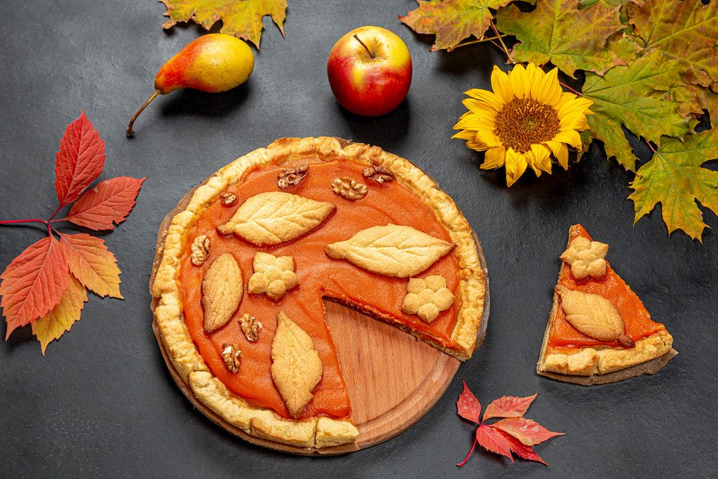 Beautiful decorated pumpkin pie on black background with autumn leaves, apple and sunflower flower