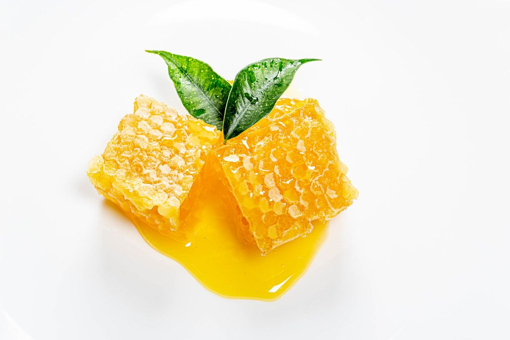 Bee honeycomb and honey with fresh green tea leaves
