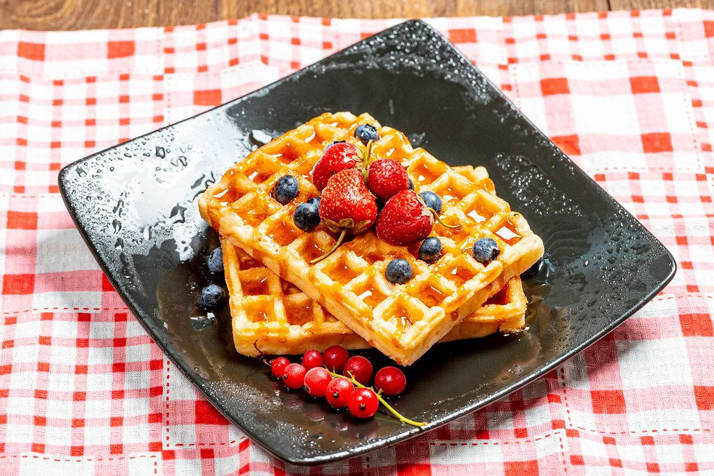 Belgian waffles with blueberries, strawberries and red currants on a black plate (Flip 2019)