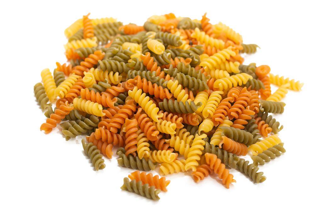 Berg von noch nicht gekochter, dreifarbiger Fusilli Pasta isoliert vor weißem Hintergrund