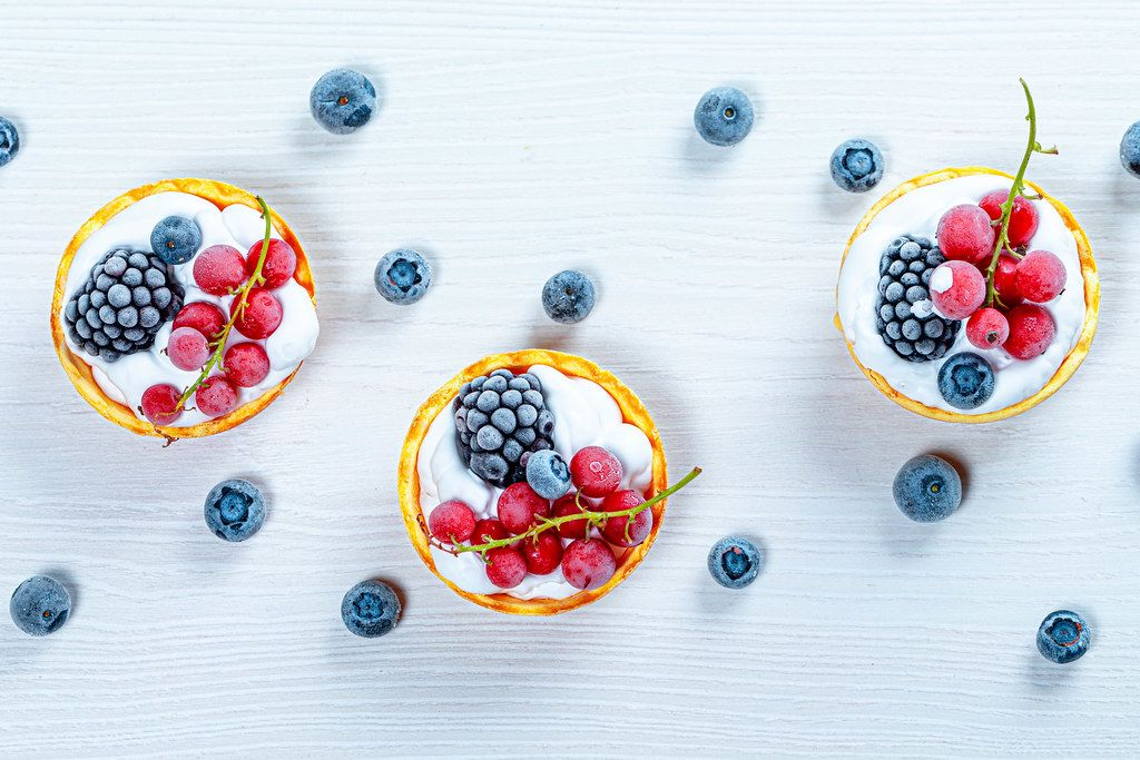 Berry cakes on a white wooden background. Top view (Flip 2019)