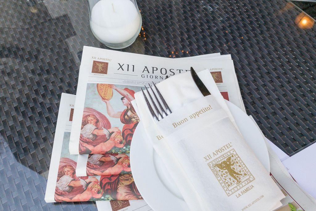 Besteck in einer Serviette, Teller und Zeitung im XII Apostel Albergo Hotel