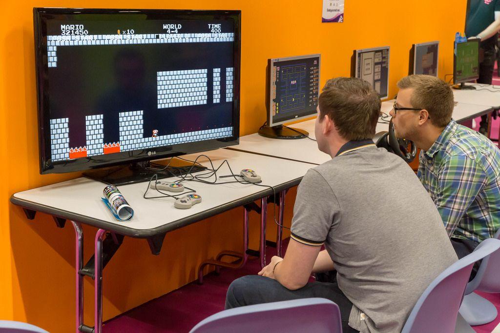 Besucher spielen Super Mario World auf der Super Nintendo SNES Konsole