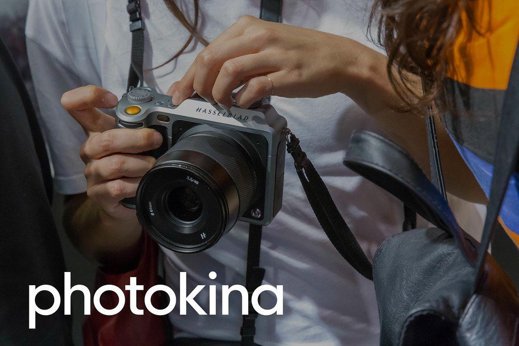 Besucher testen eine Hasselblad Kamera neben der Bildaufschrift