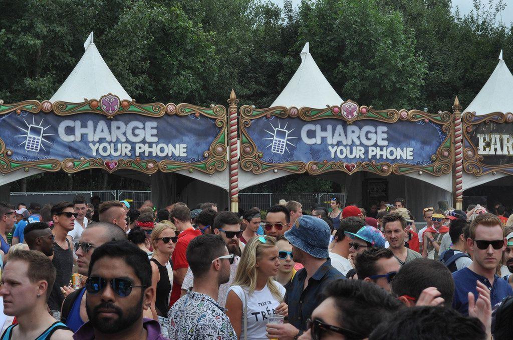 Besucher vor den Ständen mit Handy-Ladestationen - Musikfestival Tomorrowland 2014