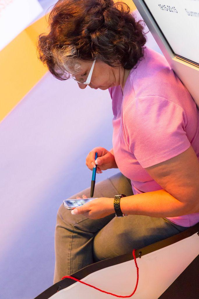 Besucherin entspannt sich und verwendet Kugelschreiber als Stylus - Gamescom 2017, Köln