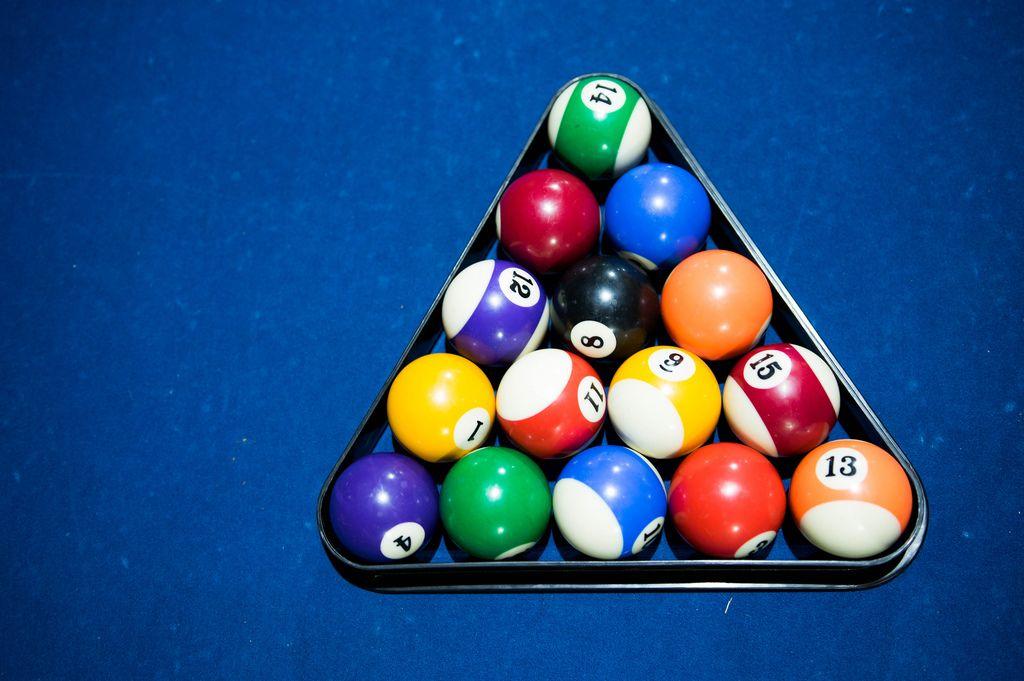 Billardkugeln im Dreieck aufgebaut, auf einem blauen Billardtisch, aus der Vogelperspektive