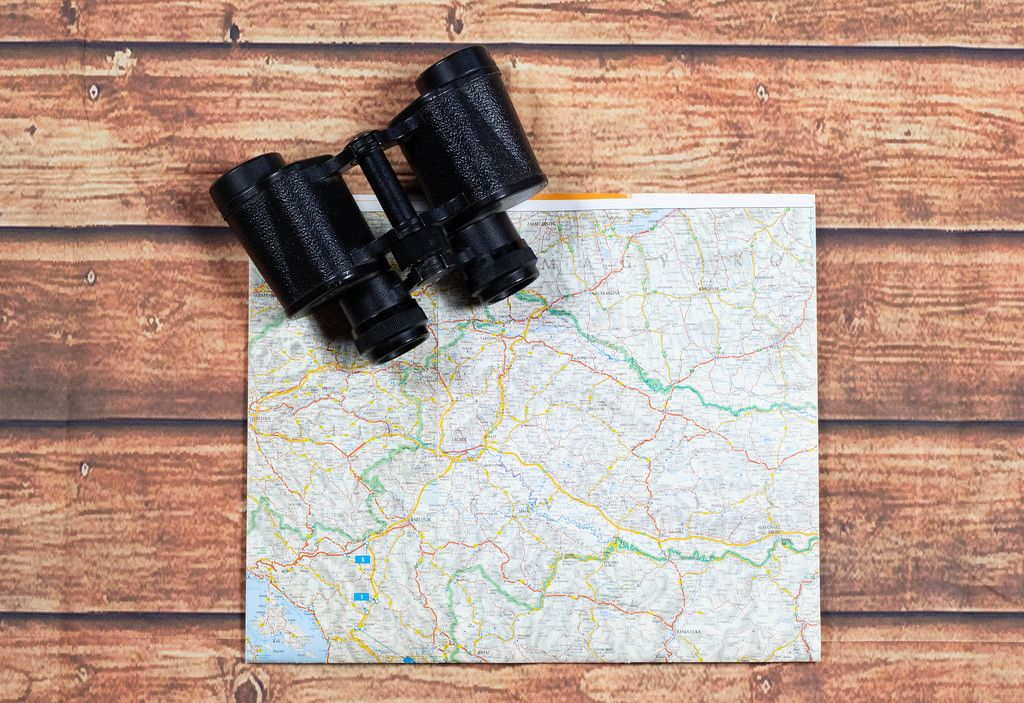 Binoculars and map on wooden table