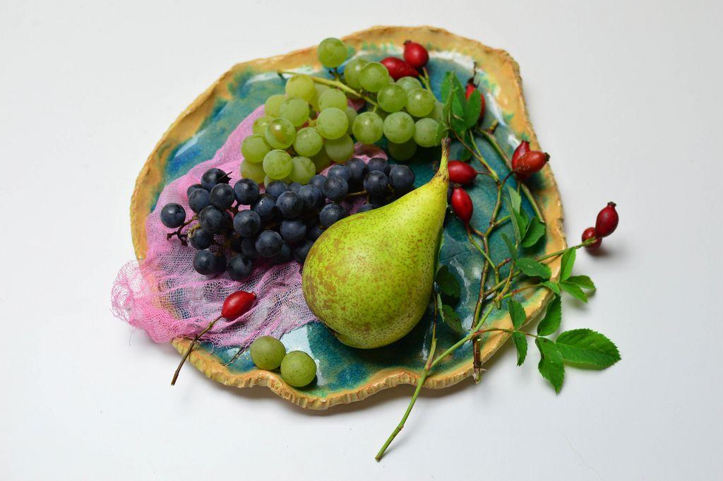 Birne mit gemischten Weintrauben auf blauem Tonteller