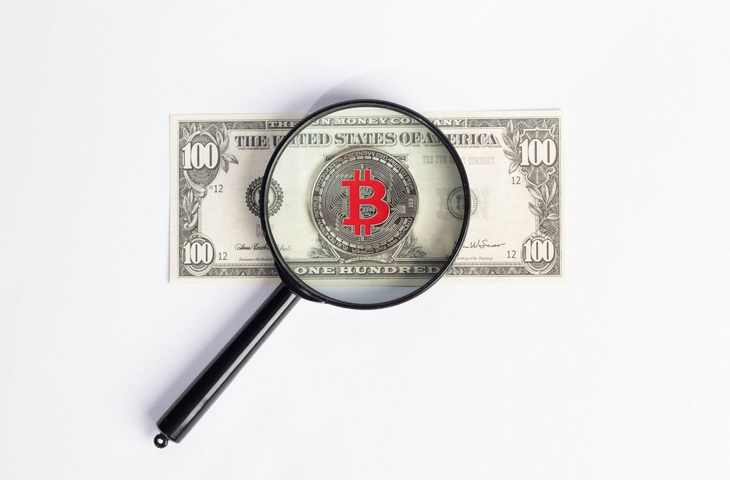 Bitcoin and magnifying glass