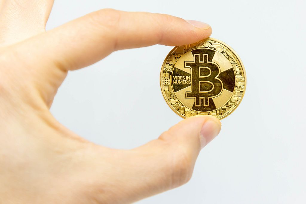 Bitcoin in a hand and white background