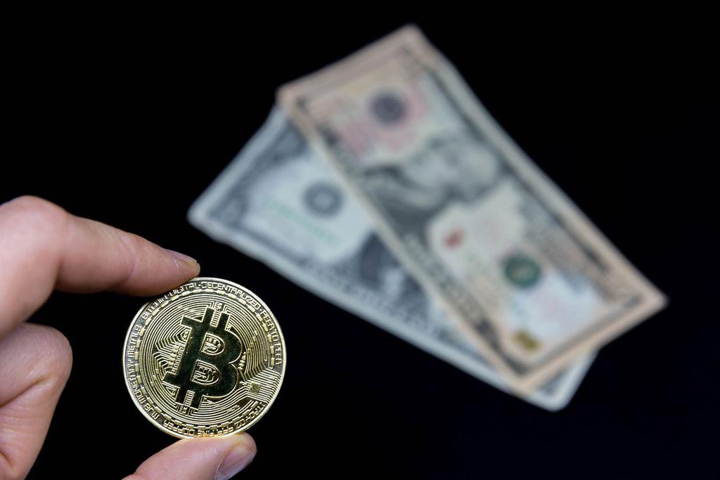 Bitcoin-Münze mit Geldscheinen im Hintergrund