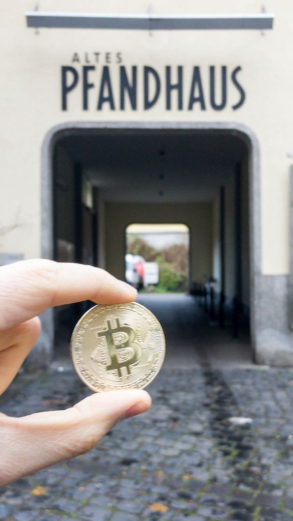 Bitcoin Münze und Altes Pfandhaus im Hintergrund