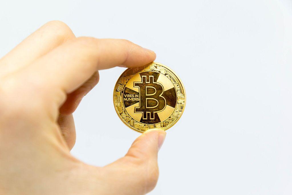 Bitcoin vor weißem Hintergrund in der Hand gehalten