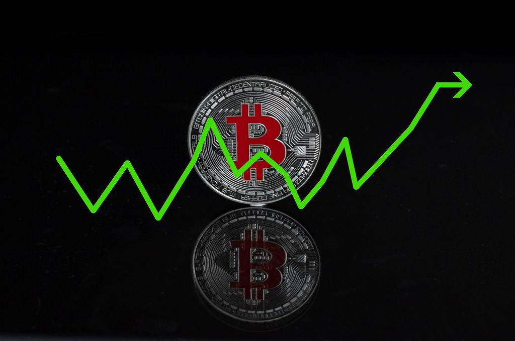 Bitcoin Wachstumsrate als Konzept mit einer silbernen Bitcoin-Münze auf schwarzem Hintergrund