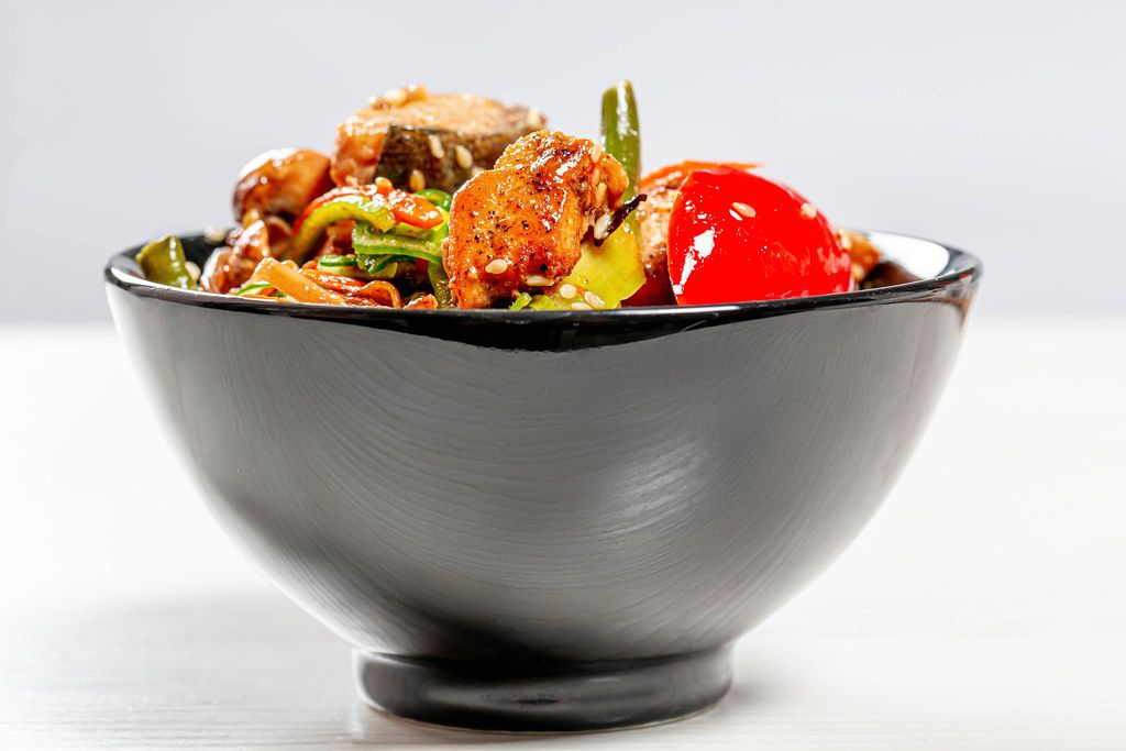 Black bowl full of Chinese buckwheat noodles with vegetables and tuna